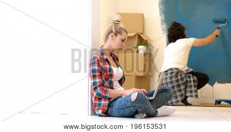 Happy couple doing home renovations, the man is painting the room and the woman is relaxing on the floor and connecting with a laptop