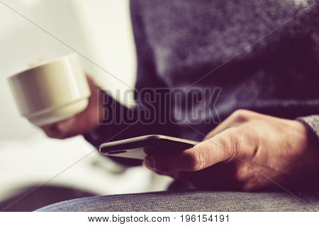 closeup of a young caucasian man with a cup of coffee in one hand and his smartphone in the other
