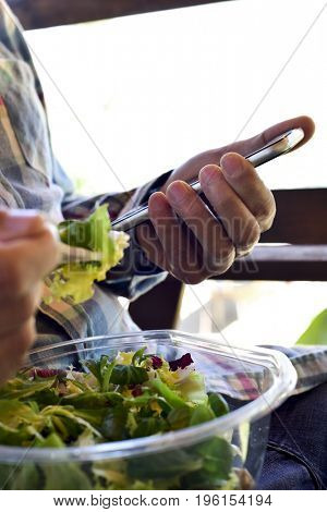 closeup of a young caucasian man wearing a plaid shirt eating a prepared salad while is checking his smartphone
