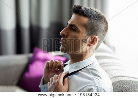 people concept - businessman taking off his tie at hotel room