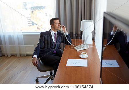 business trip, people and communication concept - businessman with coffee and papers calling on desk phone at hotel room