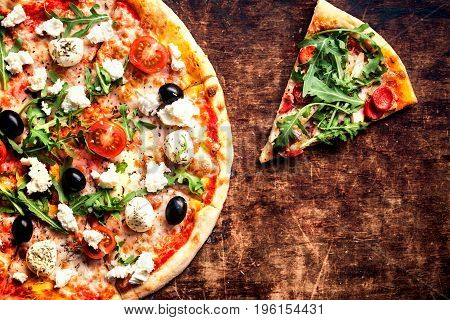 Fresh baked Hot pizza slice with cheese on a rustic wooden table closeup