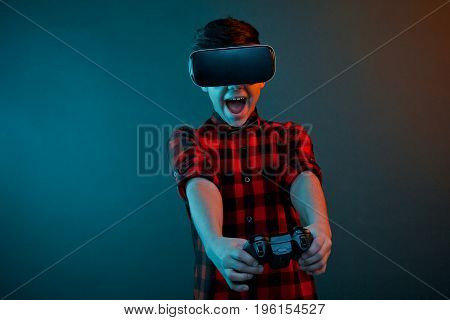 Kid in checkered shirt wearing VR glasses and playing with gamepad on dark background.