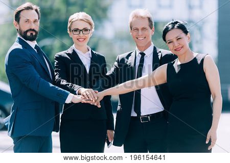 Professional Team Of Middle Aged Multiethnic Businesspeople Stacking Hands And Smiling At Camera