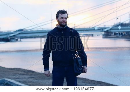 Young man on the embankment and bridge on the backstage.