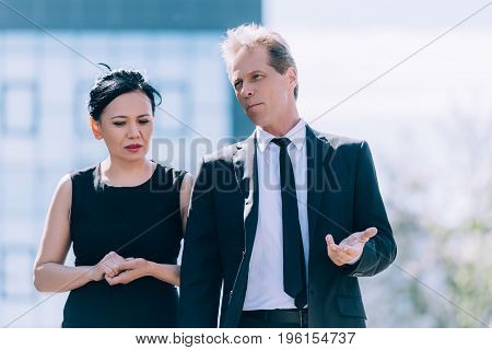 Multiethnic Business Colleagues In Formal Wear Walking And Talking Outside