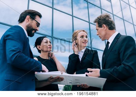 Professional Group Of Multiethnic Businesspeople Having Discussion Near Modern Office Building