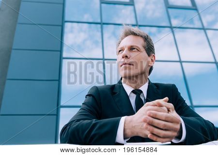 Low Angle View Of Pensive Mature Businessman Looking Away While Standing Outside Office Building