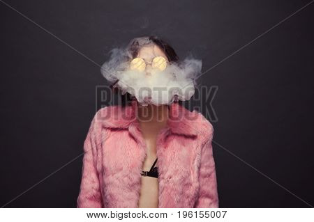 Young brunette in sunglasses and pink fur coat breathing out smoke in black background.