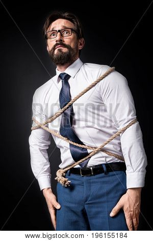 Scared Middle Aged Businessman In Eyeglasses Standing Tied With Rope Isolated On Black