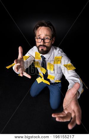 Frustrated Middle Aged Businessman With Sticky Notes On Clothes Asking For Help And Looking At Camer