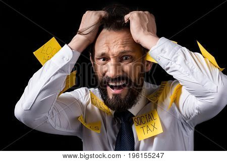 Overworked Stressed Businessman With Sticky Notes On Clothes Tearing Hair Isolated On Black