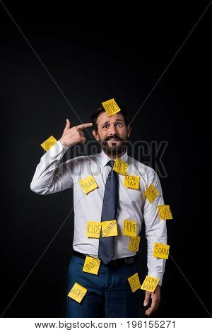 Confused Middle Aged Businessman With Sticky Notes On Clothes Gesturing Hand Gun Sign Isolated On Bl