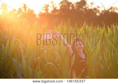 Forty Years old woman in corn. Smiling woman with a  hat in corn at sunset