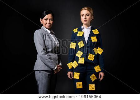 Confident Asian Businesswoman Standing Near Stressed Female Colleague With Sticky Notes On Clothes L