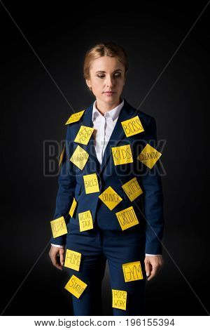 Overworked Middle Aged Businesswoman Standing With Sticky Notes On Suit Isolated On Black