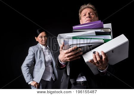 Serious Asian Businesswoman Looking At Male Colleague Holding Pile Of Folders Isolated On Black