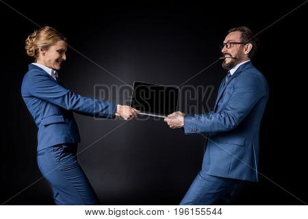 Side View Of Middle Aged Business Colleagues Fighting For Laptop Isolated On Black