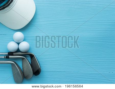 Golf concept : Golf clubs golf balls cap on blue wooden table with copy space.