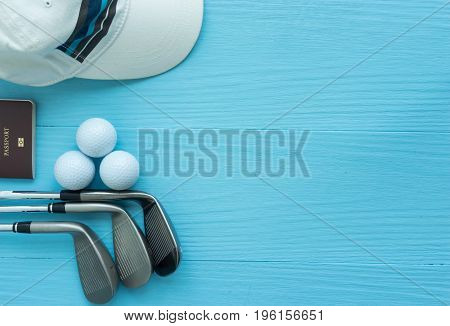 Golf concept : Golf clubs, golf balls, cap, passport on blue wooden table with copy space.
