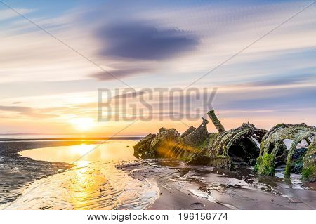 Old submarine wreck sits on the beach at low tide. summer evening sunset