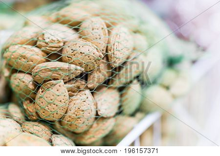 Raw Unshelled Almonds In Green Mesh Bags For Sale