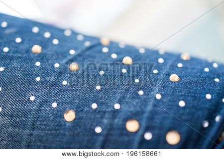 Macro closeup of jeans embellished with shiny rhinestones