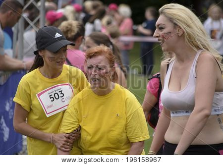COLCHESTER, ESSEX, ENGLAND,UK- 16 JULY 2017-  Athlete, suffering from heat exhaustion, is help by her friends at the finish line of Race for Life. This annual race is run by women to raise money for Cancer Research UK.