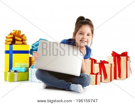 Internet shopping concept. Little girl sitting with laptop and gifts on white background