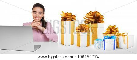 Internet shopping concept. Young woman with laptop and gifts on white background