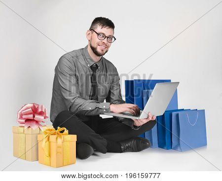 Internet shopping concept. Man with laptop and purchases on light background