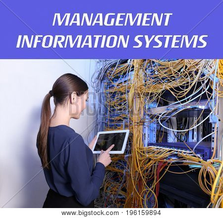 Concept of management information systems. Young engineer with tablet in server room