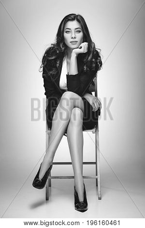 Portrait of business woman sitting on chair in studio on gray background