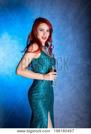 Young sexy woman with big boobs in blue elegant dress holding wineglass with champagne.
