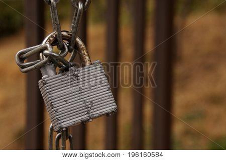 Old metal lock with chain in a garden door.
