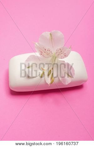 Soap and flower Alstromeria on a pink background. Spa