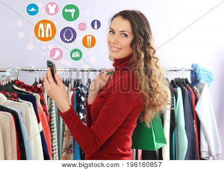 Young woman with smartphone and bag at store. Internet shopping concept
