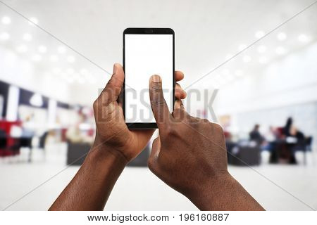 Internet shopping concept. African-American man using smartphone and blurred interior of cafe on background