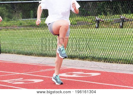 A high school teenage girl performs the A-Skip drill on a red track at track and field practice outside