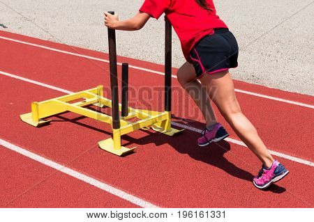 A female track and field athlete pushing a yellow sled down the track at practice for strength training