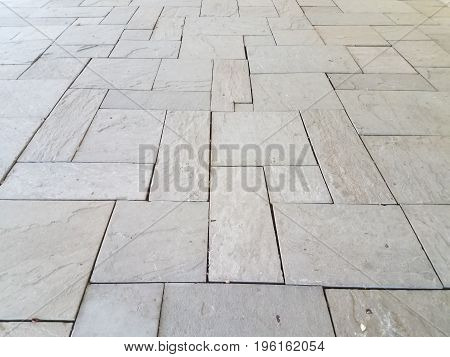 many grey rectangular and square tiles on the ground