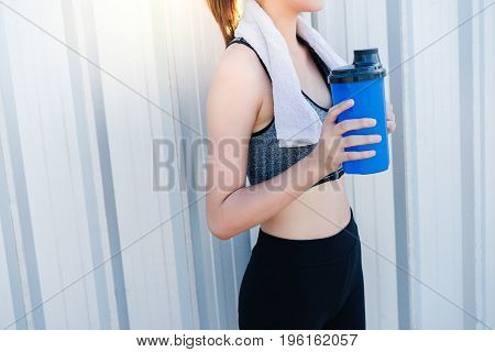Young girl asian hand holding water bottle blue and pull handkerchief on neck