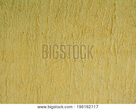 Fragment of cement yellow wall wavy structure