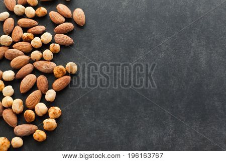 Assortment of nuts on black background with free space for text. Healthy snack for keeping you in good shape. Perfect to eat with beer.