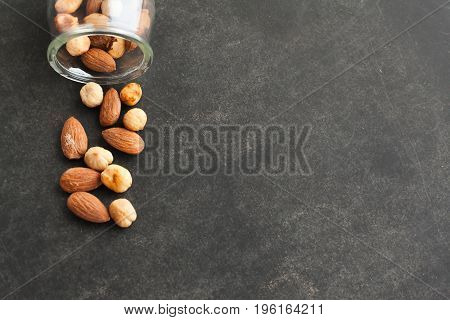 Assortment of nuts in a jar on dark background with free space for text. Healthy snack for beer.