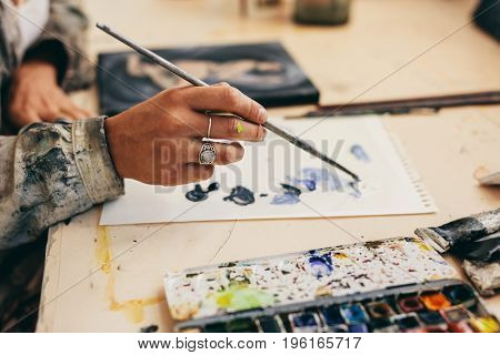 Female Artist's Hand Mixing Colors On Paper