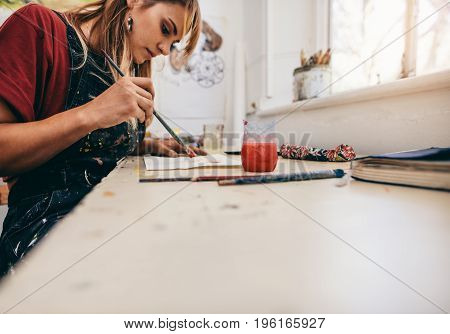 Image of beautiful woman drawing pictures in her workshop. Female artist painting in her studio.
