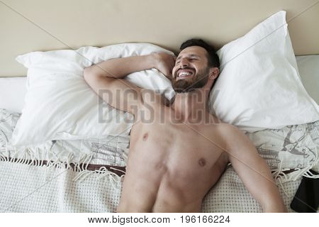 Carefree guy enjoying new day. Sexy, happy bearded man in bed.