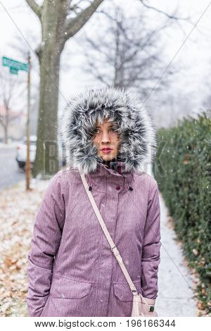 Young woman walking on sidewalk in coat during winter snow