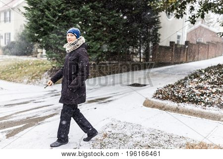 Young man with car keys walking on sidewalk in coat during winter snow